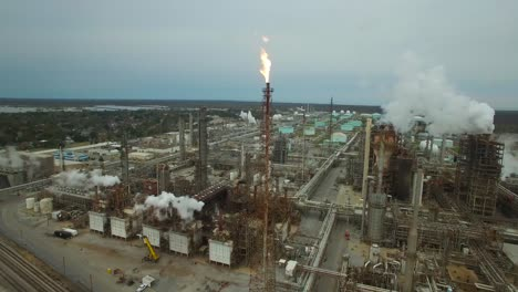 Excellent-aerial-over-huge-industrial-oil-refinery-with-gas-torch-burning-2