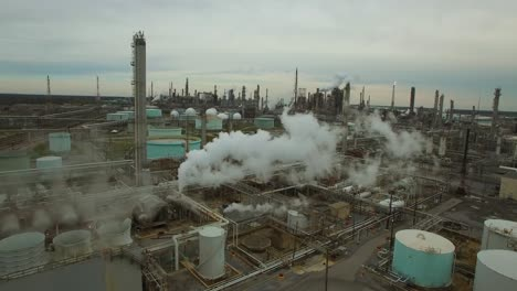 Excellent-aerial-over-huge-industrial-oil-refinery-with-smoke-and-pollutants-rising