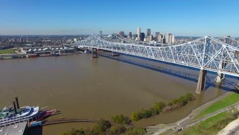 Toma-Aérea-Del-Puente-De-La-Ciudad-De-Crescent-Sobre-El-Río-Mississippi-Revelando-El-Horizonte-De-Nueva-Orleans-Luisiana