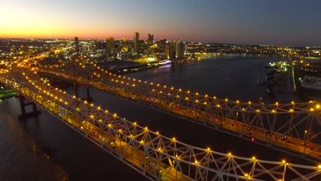 Hermosa-Noche-Toma-Aérea-Del-Puente-De-La-Ciudad-De-Crescent-Sobre-El-Río-Mississippi-Revelando-El-Horizonte-De-Nueva-Orleans-Luisiana