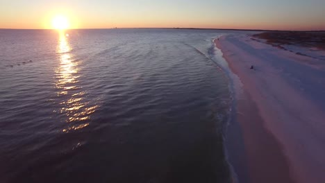 A-beautiful-aerial-shot-over-white-sand-beaches-at-sunset-following-pelicans-near-Pensacola-Florida
