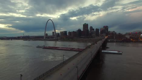 Beautiful-aerial-over-a-Mississippi-river-barge-and-bridge-with-the-St-Louis-Missouri-skyline-background