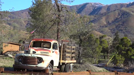 An-old-abandoned-pickup-truck-sits-beside-a-mountain-road