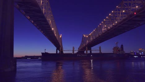 Beautiful-shot-of-a-massive-cargo-ship-traveling-under-the-Crescent-City-Bridge-at-night-with-New-Orleans-Louisiana-in-the-background