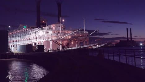 Beautiful-shot-of-a-large-Mississippi-paddlewheel-riverboat-docked-at-night-near-New-Orleans