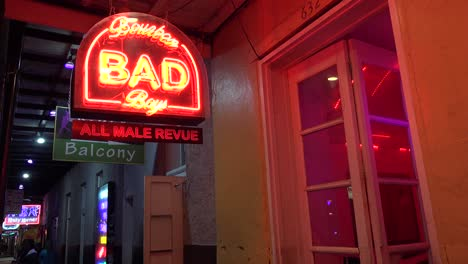 A-neon-sign-advertises-an-All-may-Revue-Bad-Boys-on-Bourbon-Street-in-New-Orleans-at-night