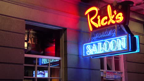Neon-sign-for-Rick-s-Saloon-on-Bourbon-Street-in-New-Orleans-at-night-and-legs-coming-out-of-window