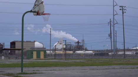 An-empty-basketball-court-stands-in-front-of-a-large-oil-refinery
