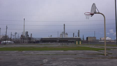 An-empty-basketball-court-stands-in-front-of-a-large-oil-refinery-1