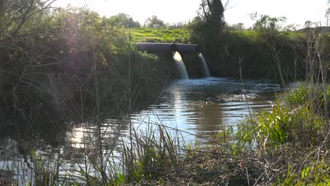 Contaminated-water-is-dumped-into-a-waterway-through-industrial-pipes