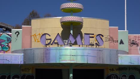 Zoom-out-from-an-abandoned-and-graffiti-covered-game-center-at-an-amusement-park-presents-a-spooky-and-haunted-image