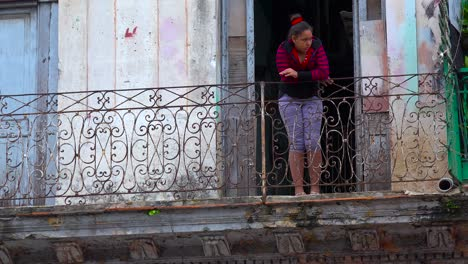 A-woman-stands-on-a-balcony-in-the-old-city-of-Havana-Cuba