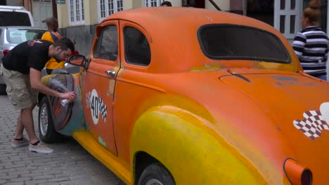 A-man-spray-paints-his-classic-old-car-on-the-streets-of-Havana-Cuba