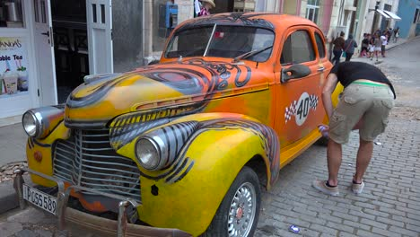 A-man-spray-paints-his-classic-old-car-on-the-streets-of-Havana-Cuba-1