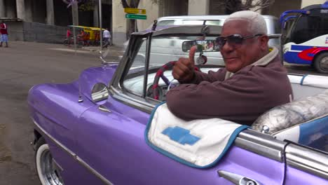 Classic-old-cars-are-driven-through-the-colorful-streets-of-Havana-Cuba-5