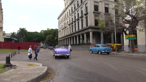 Classic-old-cars-are-driven-through-the-colorful-streets-of-Havana-Cuba-6