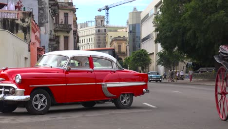 Classic-old-cars-and-horse-carts-are-driven-through-the-colorful-streets-of-Havana-Cuba