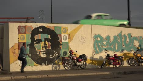A-car-drives-down-a-road-near-a-building-decorated-with-Che-revolutionary-painting-in-Communist-Cuba