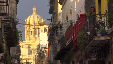 A-woman-stands-on-a-balcony-overlooking-the-old-city-of-Havana-Cuba