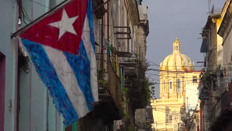 The-Cuban-flag-flies-in-front-of-a-scene-in-the-Old-City-of-Havana-Cuba