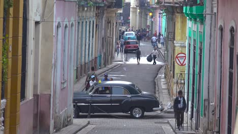 Old-cars-are-parked-along-a-narrow-street-in-the-old-city-of-Havana-Cuba