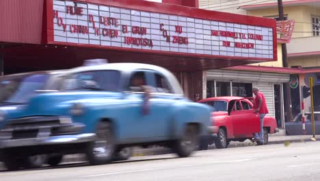 Men-load-up-an-old-car-outside-a-movie-theater-in-Havana-Cuba