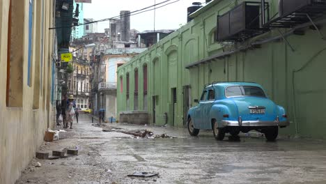People-walk-on-the-old-city-of-Havana-Cuba-in-the-rain-with-classic-old-car-foreground