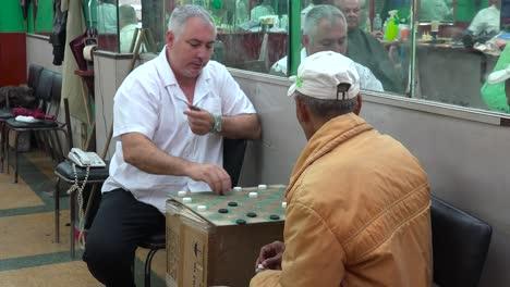 Zwei-Männer-Spielen-Dame-In-Einem-Friseurladen-In-Havanna-Kuba