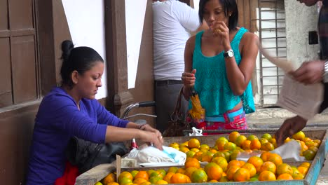 A-woman-sells-fruit-from-a-cart-along-the-street-in-havana-Cuba