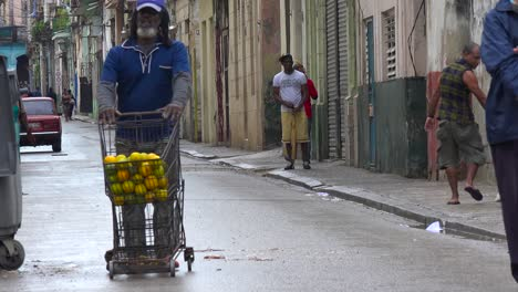 A-street-vendor-wheels-his-goods-down-a-street-in-the-old-city-of-Havana-Cuba