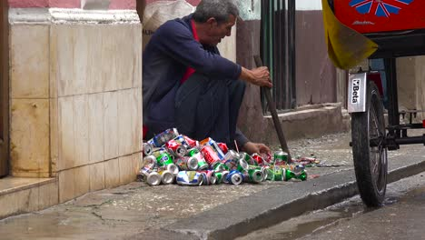 A-man-on-the-street-crushes-and-recycles-aluminum-cans-in-Havana-Cuba
