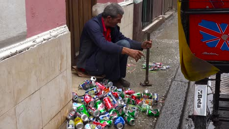 A-man-on-the-street-crushes-and-recycles-aluminum-cans-in-Havana-Cuba-1