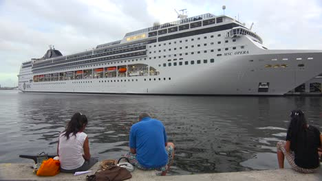 Massive-cruise-ships-dock-at-Havana-harbor-Cuba-as-Cuban-onlookers-gather-to-marvel-at-it