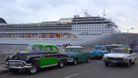 Massive-cruise-ships-dock-at-Havana-harbor-Cuba-with-classic-old-cars-in-the-foreground