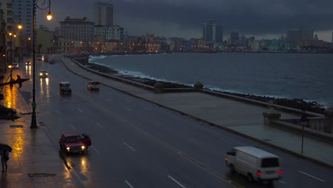 Beaytiful-shot-of-cars-traveling-on-the-waterfront-Malecon-in-Havana-Cuba-at-night