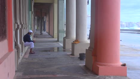 A-man-sits-under-a-walkway-in-Havana-Cuba-taking-shelter-from-a-big-storm