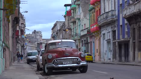Great-shot-of-crowded-streets-and-alleys-of-the-old-city-of-Havana-Cuba-with-classic-old-car-foreground