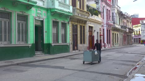 A-street-vendor-walks-down-a-boulevard-in-Havana-Cuba-selling-his-wares