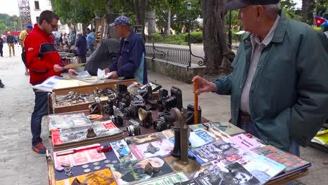 Verkäufer-Auf-Den-Straßen-Von-Havanna-Kuba-Verkaufen-Alte-Kameras-Radios-Und-Propagandabücher-Und-Poster