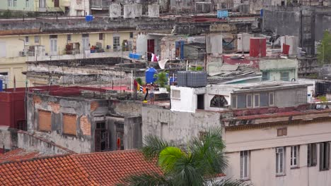 Zoom-out-from-woman-doing-laundry-reveals-the-skyline-of-Havana-Cuba