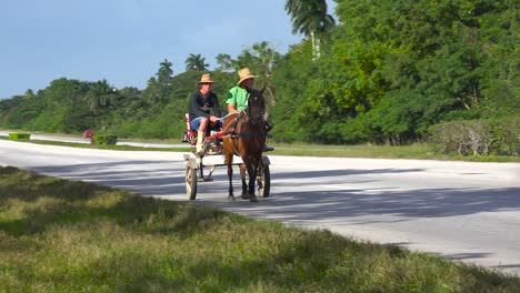 Horse-carts-move-along-a-highway-in-Cuba