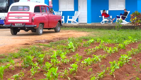 Establishing-shot-of-a-Cuban-tobacco-farm-house-with-kids-on-rocking-chairs-on-porch