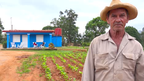 A-Cuban-farmer-stands-in-front-of-a-farm-house-on-a-tobacco-farm-in-Vinales-Cuba