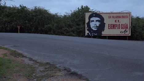 Communist-propaganda-billboards-line-a-road-in-Cuba-with-classic-old-car-passing