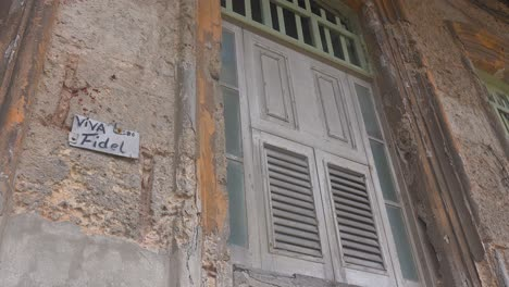 Old-decaying-windows-on-a-building-in-Havana-Cuba-with-a-sign-saying-Viva-Fidel