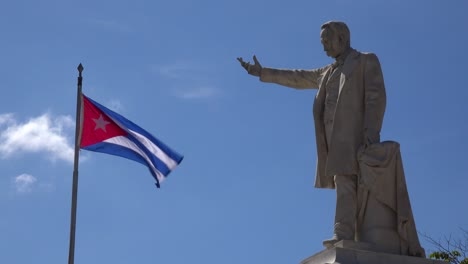 The-flag-of-Cuba-flies-in-the-sky-with-a-statue-of-Jose-Marti-in-the-foreground