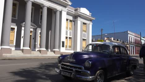 A-large-stately-building-stands-in-the-central-square-of-Cienfuegos-Cuba-with-classic-old-car-foreground