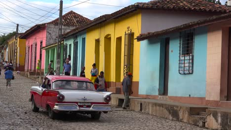 A-beautiful-shot-of-the-buildings-and-cobblestone-streets-of-Trinidad-Cuba-with-old-classic-car-passing