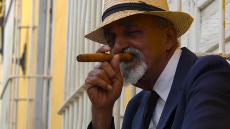 A-cuban-man-smokes-a-cigar-on-the-colorful-streets-of-Trinidad-Cuba