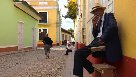 A-cuban-man-smokes-a-cigar-on-the-colorful-streets-of-Trinidad-Cuba-1